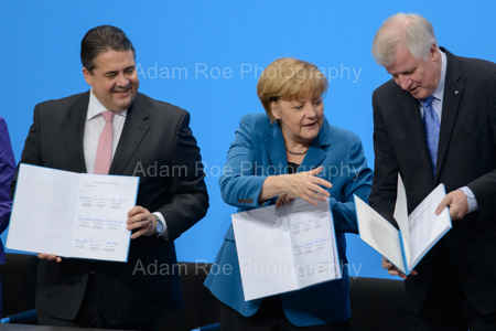 The party heads with their signed copies of the coalition contract. Merekel (CDU) helps Seehofer (CSU) while he struggles a bit and Gabriel (SPD) laughs on