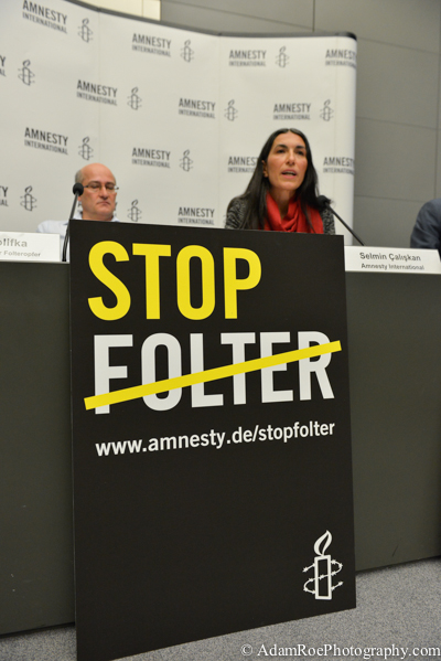 "Matthias Polifka and Selmin Caliskan at the press conference, behind a sign that reads ""Stop Torture""."