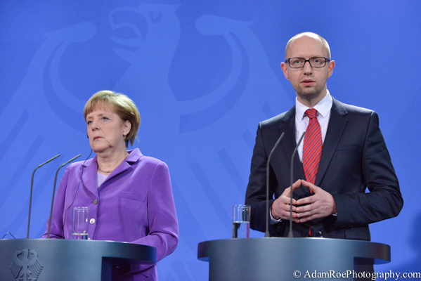 Angela Merkel and Arseniy Yatsenyuk. She listens while he mimics her famous hands.
