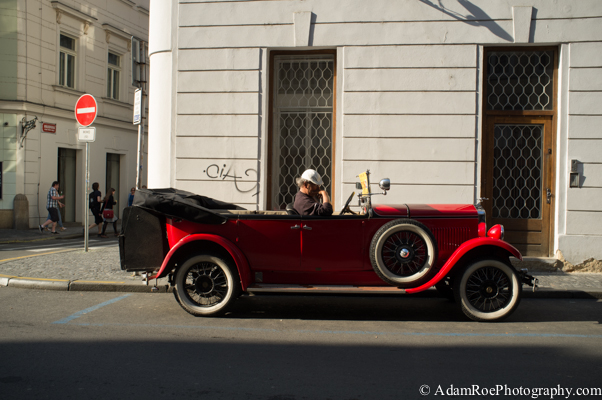 A driver takes a break from ferrying tourists around town in a classic red convertible.
