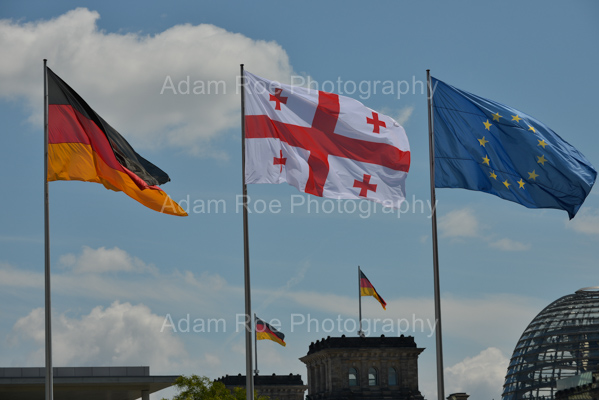 The flags of Germany, Georgia and the European Union fly at the Federal Chancellory. The German Bundestag and its flags are in the background.