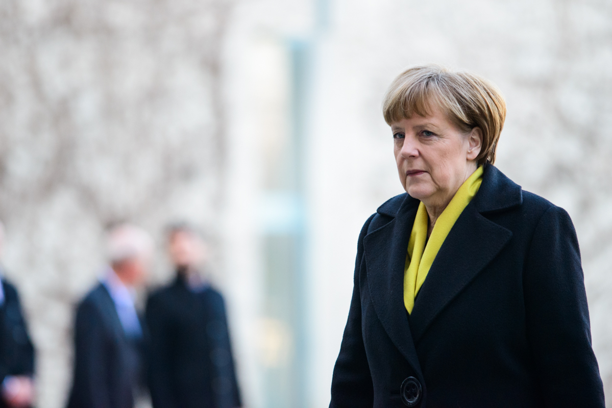 Angela Merkel strolls through the yard at the chancellery.