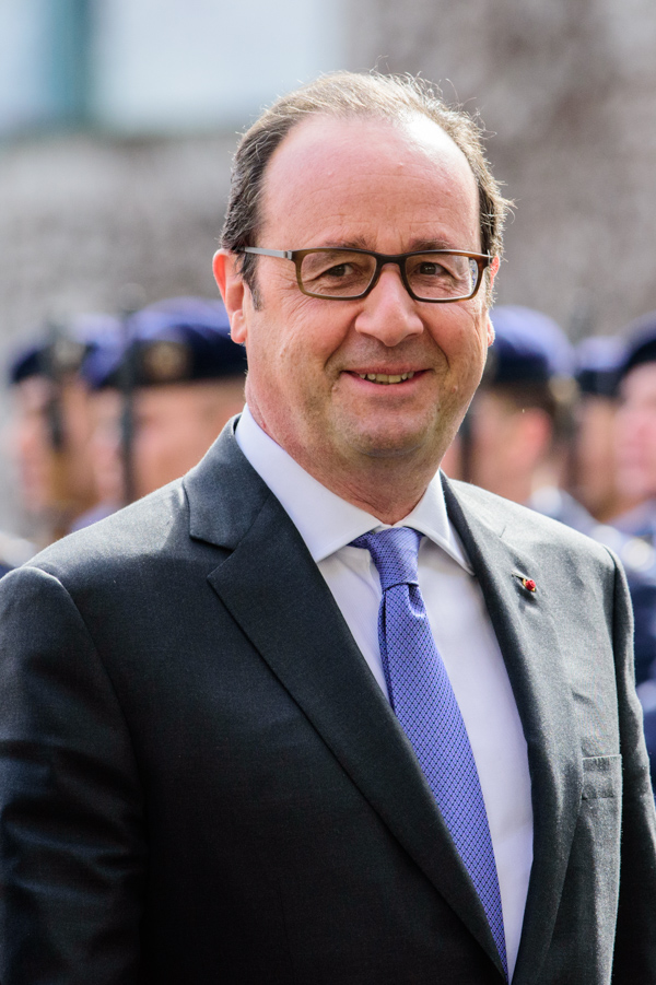 Francois Hollande stroll through the courtyard at the German Federal Chancellery.