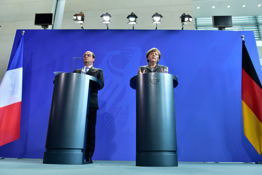 Flags, Podiums, Politicians: Francois Hollande and Angela Merkel address the press together.