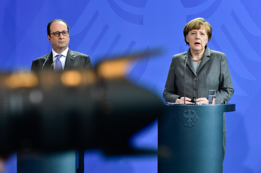 When press conferences go on too long, we get restless. The AFP photographer next to me was aiming for reflections in the glass, I went for his lens crossing Hollande towards Merkel.