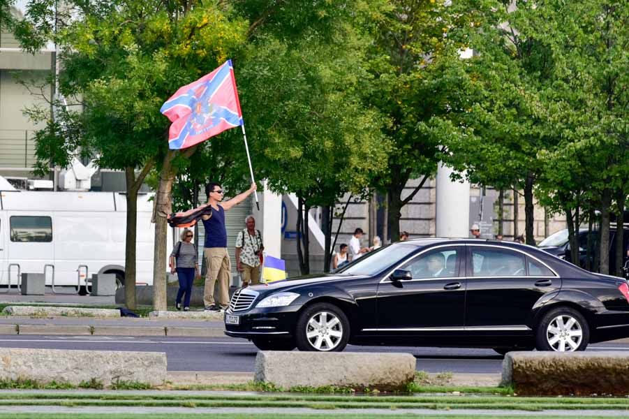 An odd welcome: A man waves the separatist flag of Novorossiya in Berlin as the motorcade carrying Ukrainian President Petro Poroshenko passes by en route to Merkel's offices.