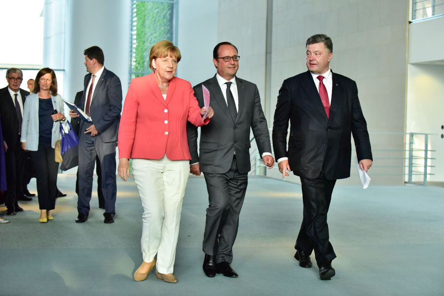 Merkel, Hollande and Poroshenko stroll towards the press conference.