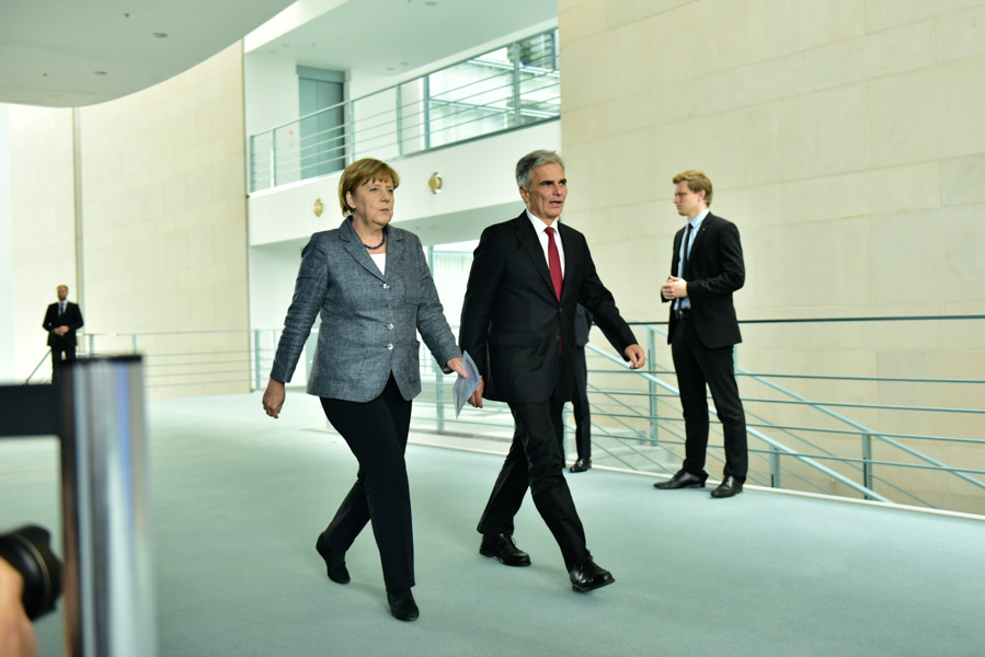 Merkel and Austrian Prime Minister Werner Faymann stroll to their press conference.